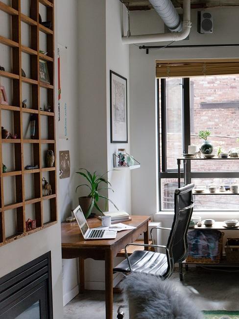Bureau à la maison avec étagère et décoration devant une grande fenêtre