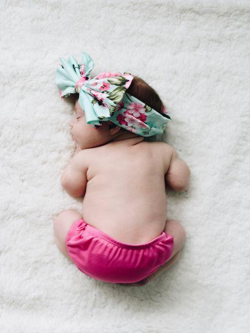 nouveau-ne en couche-culotte rose et un grand nœud sur la tete dort paisiblement allongé sur une matiere blanche duveteuse