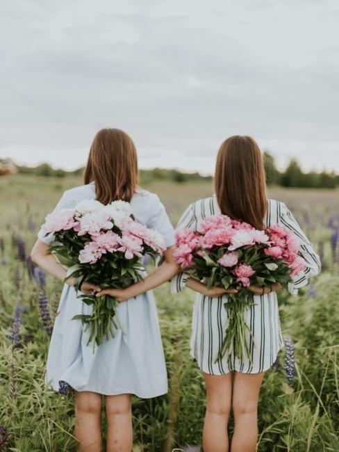 deux jeunes femmes dans les champs avec un bouquet de fleurs