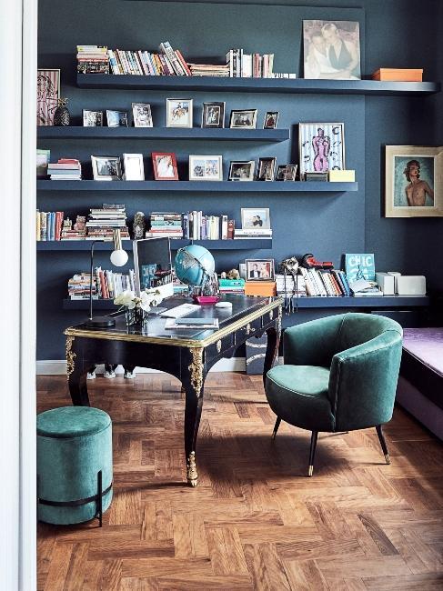 Bibliotheque sur mur bleu et fauteuil vert velours