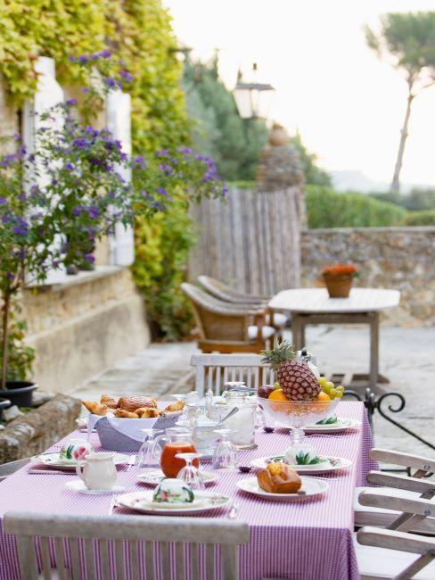 Table de jardin préparée pour le brunch avec nappe lilas