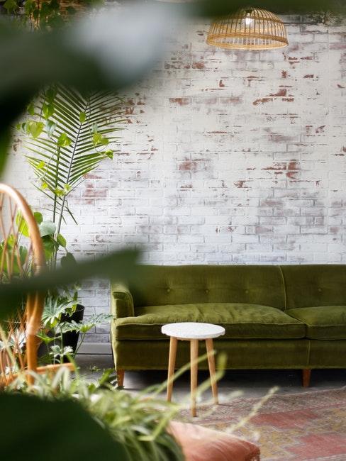 Salon avec mur en brique blanche, canapé en velours vert, tabouret en bois et plante verte