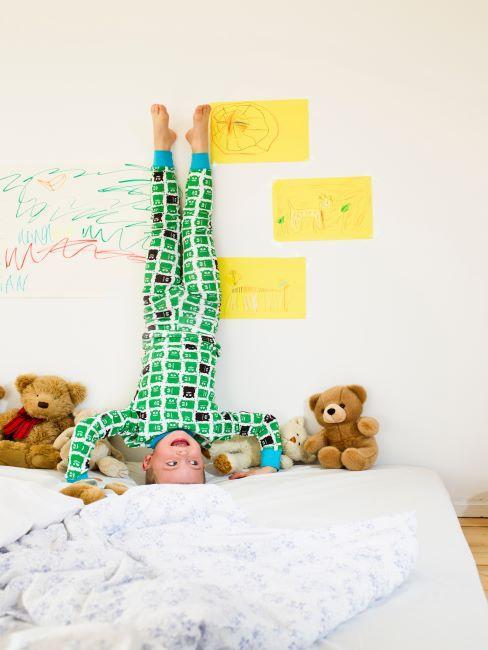 Garçon en pyjama vert faisant le poirier sur son lit
