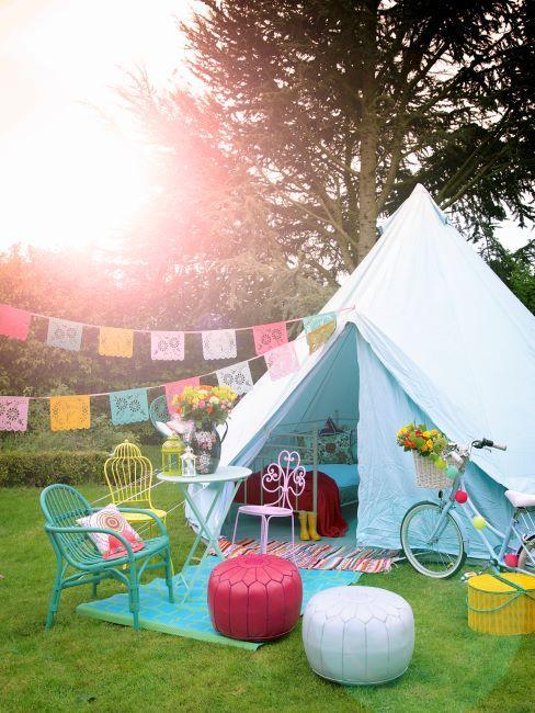 Tente blanche sur gazon vert, détails déco de couleurs vives et pastel