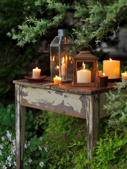 Table vintage avec différentes lanternes et bougies allumées