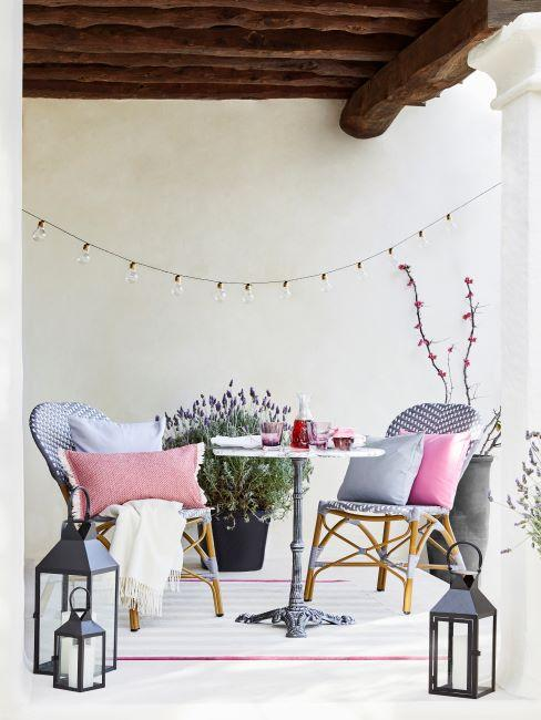 petit salon de balcon avec chaises en cannage et coussins