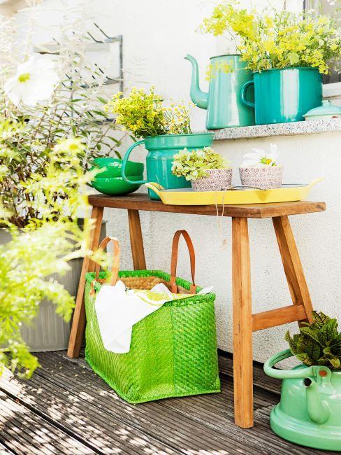 Banc en bois sur balcon avec panier vert, cache-pots turquoise avec fleurs jaunes