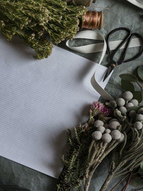 fleurs sechees, ciseaux, ruban et feuille de papier
