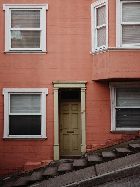 Maison a facade couleur abricot et fenetres blanches