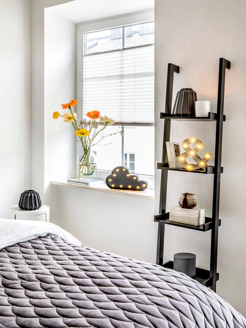 Decoraties op zwarte ladderkast naas het raam met transparante vaas met bloemen