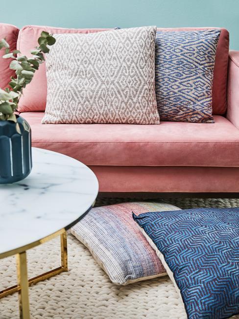 Roze zitbank met sierkussens naast een salontafel uit marmer met groene vaas met bloemen