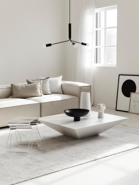 Een moderne woonkamer met witte zitbank met witte kussens en witte bijzettafel in betonlook