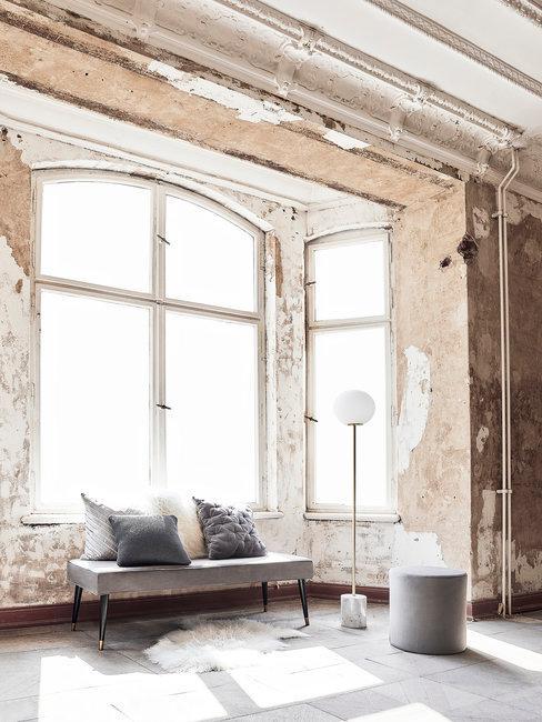 Loft met onafgewerkte wanden met grijze bankje en poef