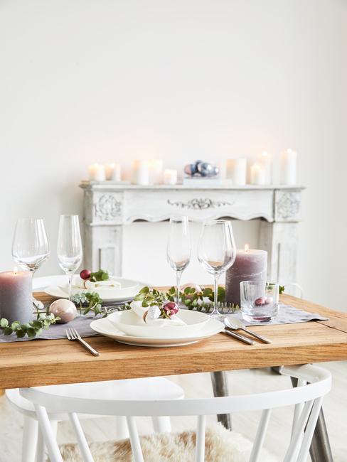 Wit serviesgoed en zilveren bestek, hoge kandelaars en sparren takken als decoratie