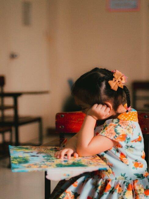 Meisje in kleurrijke outfit leest boek aan tafel