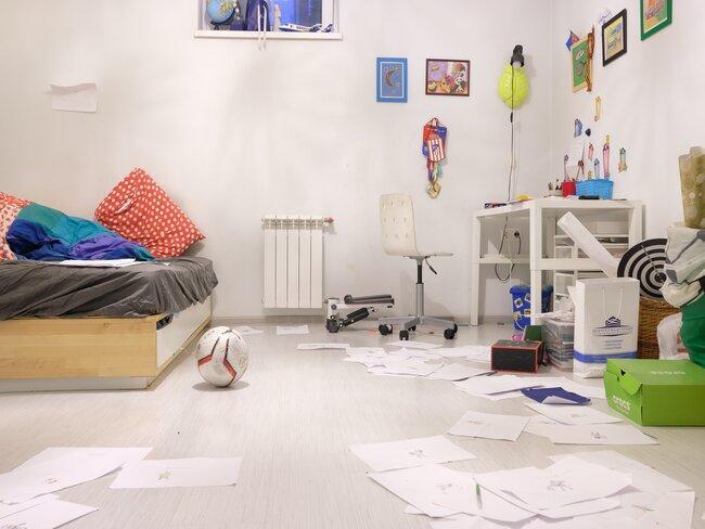 jongens slaapkamer met houten bed, witte muur en wit bureau, gekleurde decoratie en papier op de grond