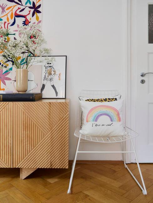 Kussen uit de Kera Till collectie op een witte stoel naast een houten dressoir.