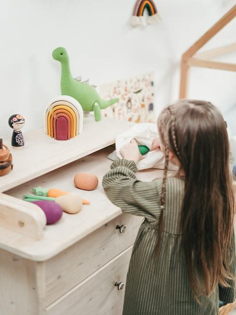 Landelijke babykamer: meisje speelt met houten speelgoed