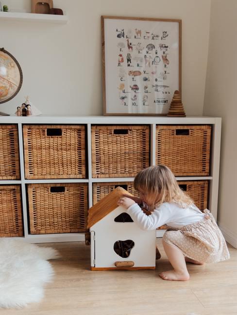 Een meisje dat speelgoed zoekt in een mand naast een witte boekenkast en een wit vloerkleed