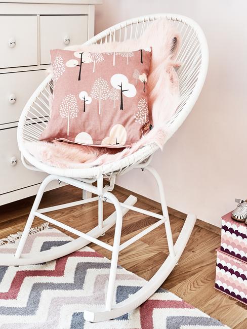 Meidenkamer: witte schommelstoel met roze sierkussen op het vloerkleed