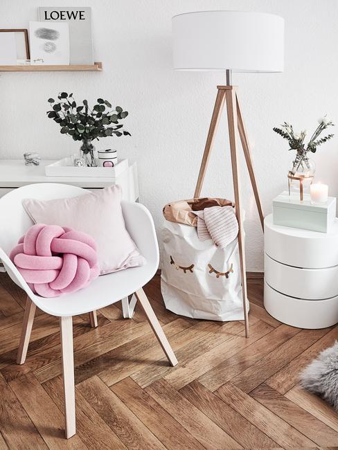 Wit fauteuil met roze decoratieve kussen naast een wit wasmandje en houten vloerlamp en wit nachtkastje