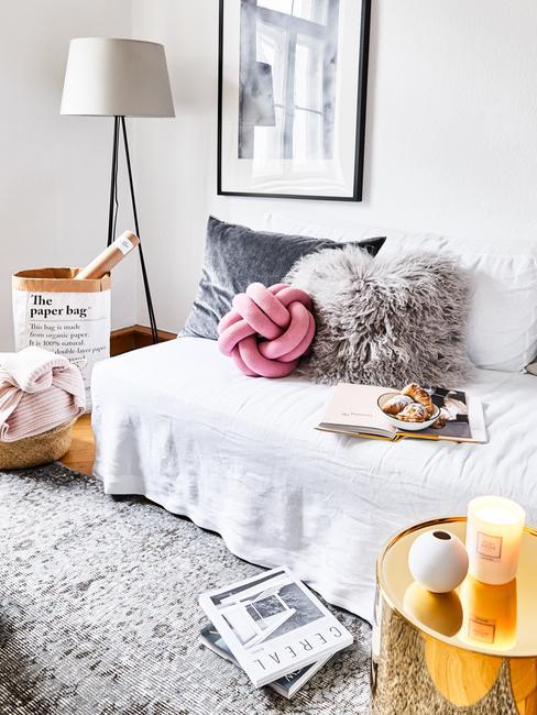 Zitbank met witte plaid en sierkussens in grijs en roze naast bijzettafel in goud kleur met kaarsen en vaas