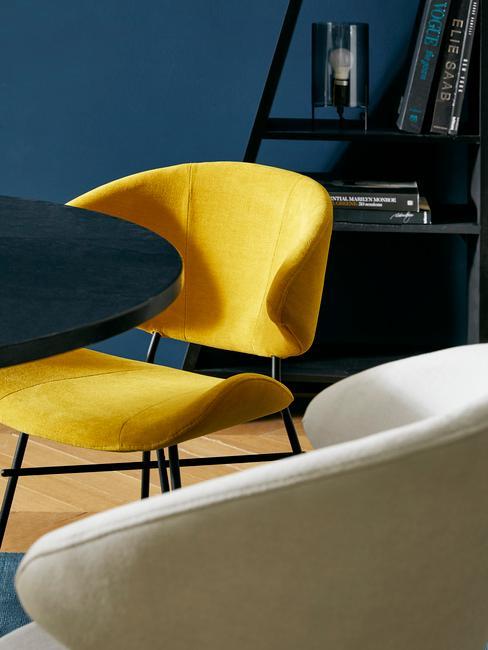 Gele corduroy fauteuil naast een zwarte tafel