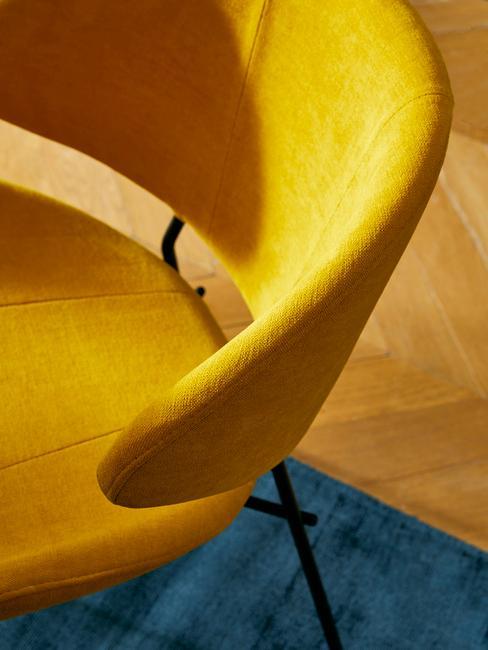 Gele corduroy fauteuil op blauw vloerkleed