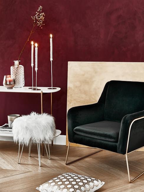 Zwarte fauteuil van geborsteld rvs naast schapenvacht kruk en witte bijzettafel met kandelaar