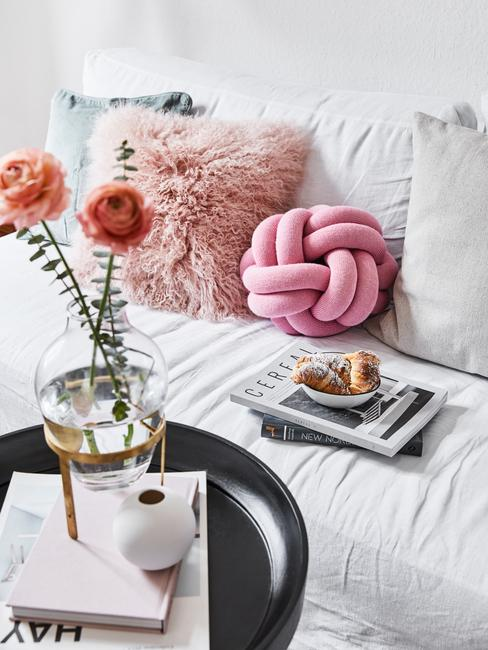 Vaas met bloemen op zwarte salontafel naast witte zitbank met sierkussens