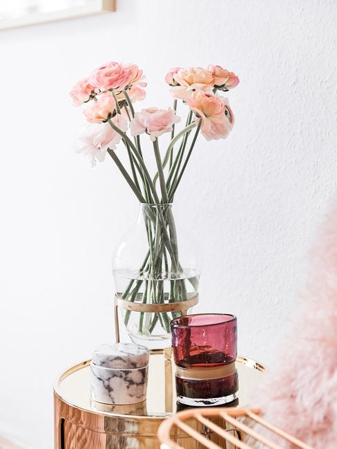 Transparant glazen vaas met bloemen op glazen bijzettafel