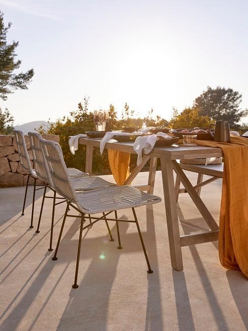 balkon inrichten houten tafel met rotan gevlochten stoelen bij ondergaande zon met okergele accessoires