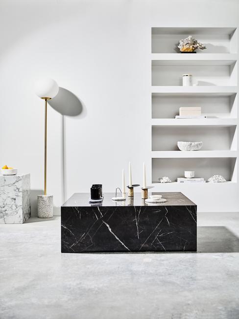 Terazzo: zwarte marmeren bijzettafel met kandelaar naast een vloerlamp en witte openkast