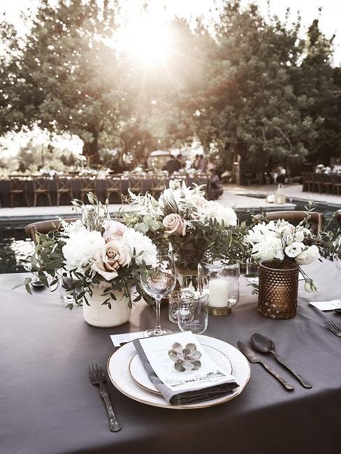 Gedekte bruiloftstafel buiten met veel kaarsen en bloemen als tafeldecoratie in boho-stijl
