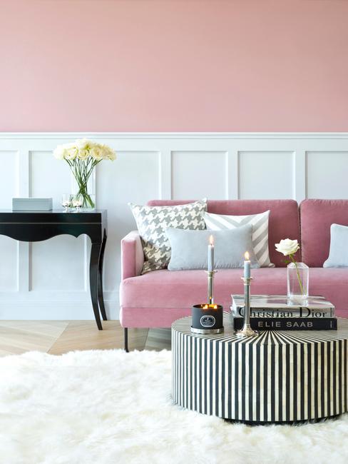 Bank reinigen: een woonkamer in roze met roze zitbank en witte vloerkleed naast zwarte bijzettafel met kandelaars en zwarte sidetable met vaas