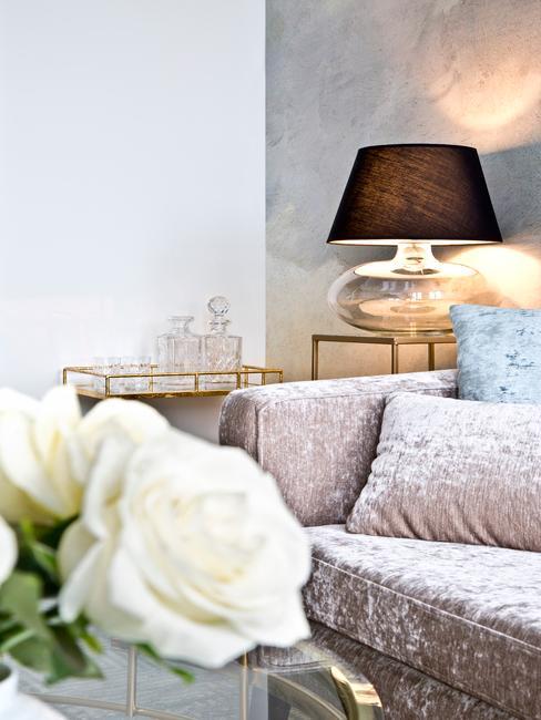 Bank reinigen: close-up velvet zitbank met sierkussens naast goudkleurige bar cast en grote tafellamp