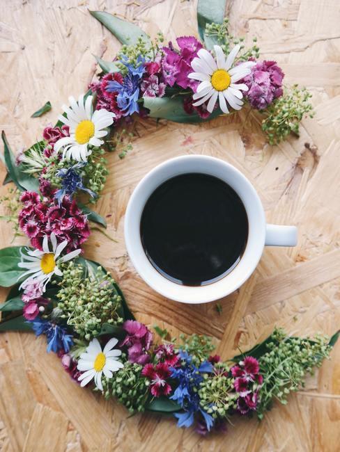 Een boho-stijl krans van vers geplukte bloemen op een houten tafel