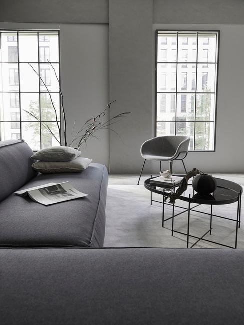 Industrieel interieur woonkamer met grijze hoekbank en zwarte bijzettafels
