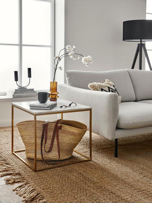 Moderne woonkamer met grijze zitbank en metalen bijzettafel met rotan mand