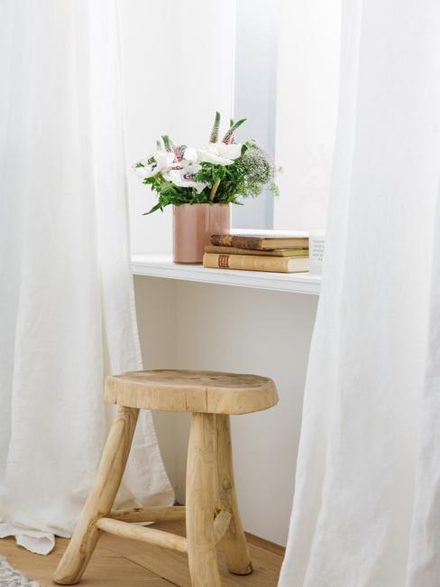 Boeken en vaas op venster met witte gordijnen naast een houten kruk