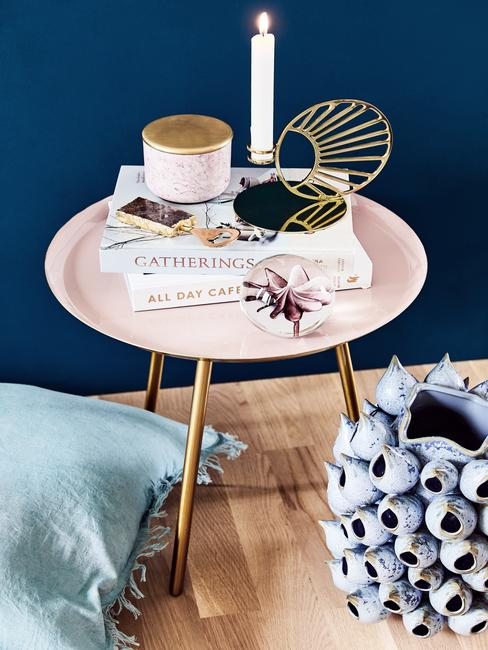 Boeken, kaarsen op roze tafel voor donkerblauwe muur
