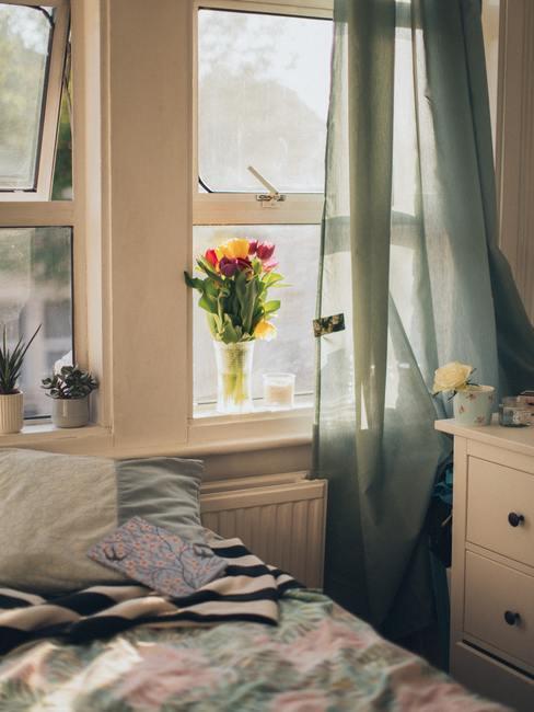 Boeket van tulpen in een transparante glazen vaas op een witte vensterbank