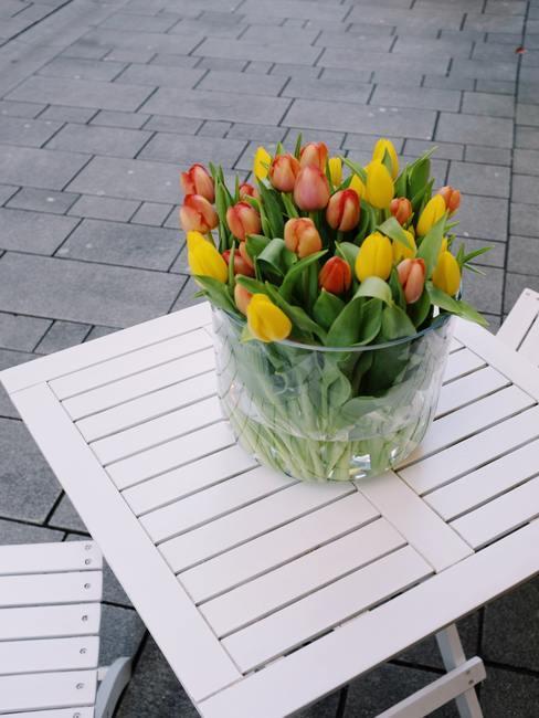 Boeket van tulpen in een transparante glazen vaas op een witte tafel