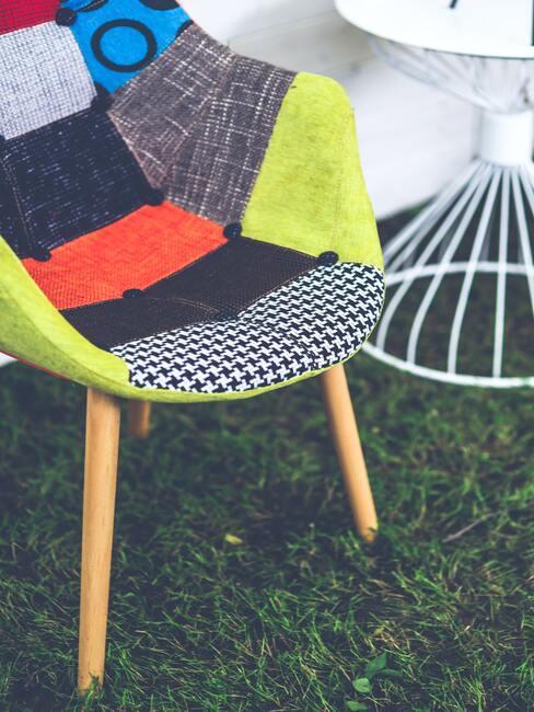 Patchwork: een fauteuil met een gekleurde bekleding naast een witte tafel