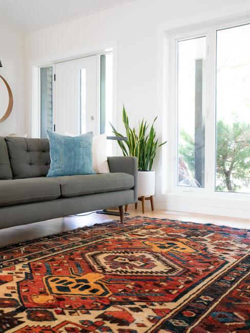Woonkamer met groot vloerkleed en grijze bank met lichtblauwe sierkussen