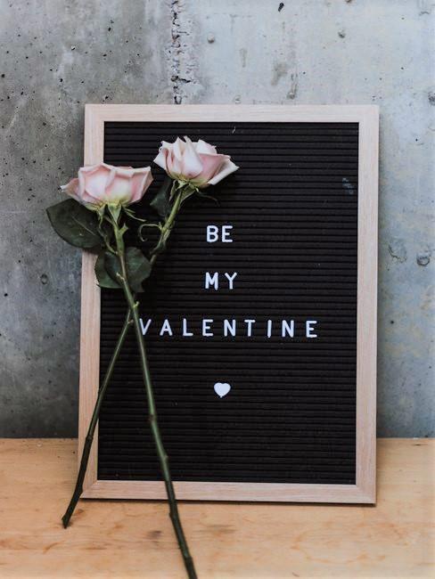 Roze rozen met letterbord op beton achtergrond