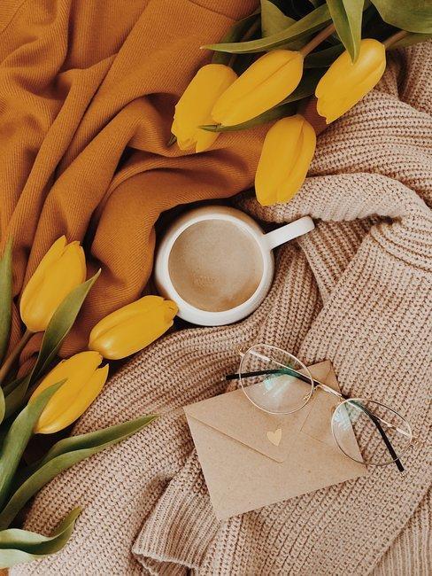 Gele tulpen met koffie, bruine kaart op bruine deken