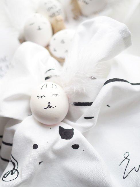 Witte paaseieren op witte handoek met zwarte details