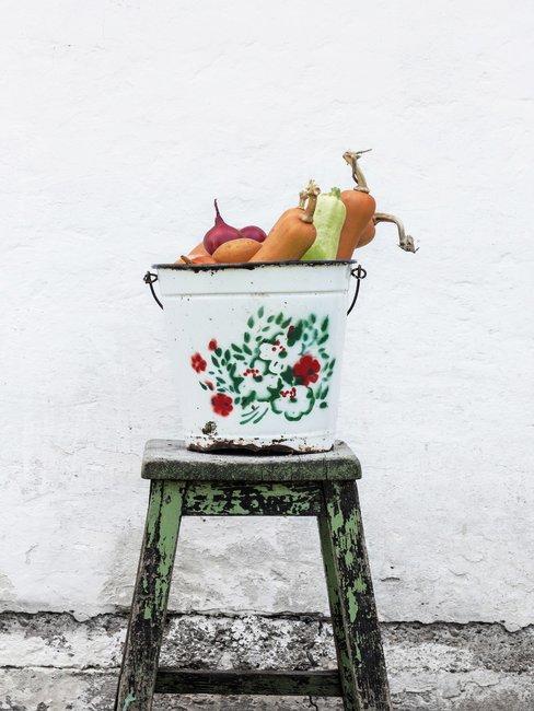 Vintage schoonmaak emmer op oude groene houten kruk gevuld met groenten