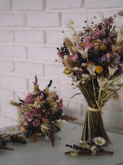 Boeket met droogbloemen voor witte tegels en op een witte tafel in boho-stijl